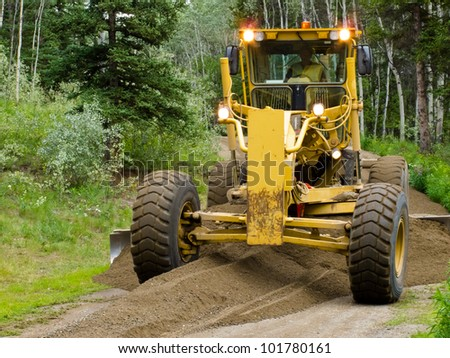 Large yellow grader resurfacing a narrow rural road through a forest with fresh gravel