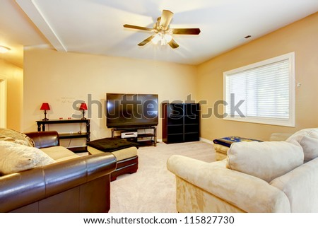 Large yellow living room with leather sofas and TV.