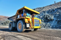 Large-yellow quarry dump trucks produce transportation of minerals
