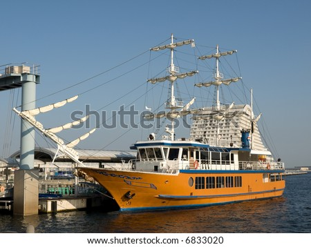 Large yellow sailing boat with white sails docked at Kobe Harborland port area near Kobe Port Tower during the day time. #6833020