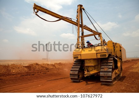 Large yellow side boom pipe layer industrial machine on orange dusty sandy outdoor construction site - stock photo