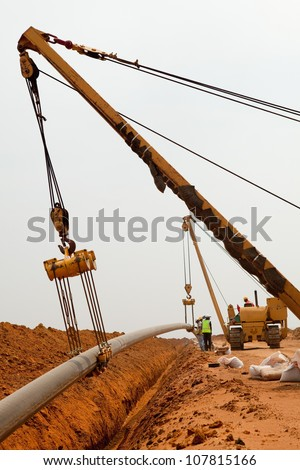 Large yellow side boom pipe layer or stringer industrial machine on orange dusty sandy outdoor construction site laying a pipe in a trench watching by workers