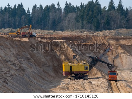 Largest mining excavator with electric shovel loading sand into dump truck in opencast. Orange mining trucks transports sand in open pit mine. Concept of the Mining industry