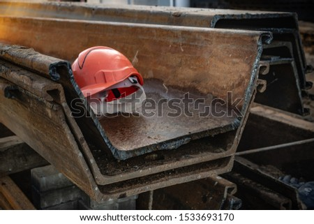 Larsen sheet piles are lying and waiting for a dive at a construction site. The builder forgot his helmet and left for lunch. Piling will continue after. #1533693170