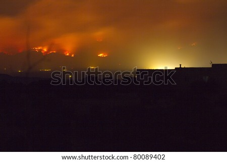 Las Conchas wildfire burns near the town of Los Alamos (yellow light) on Monday, June 27, 2011, as seen from Santa Fe County