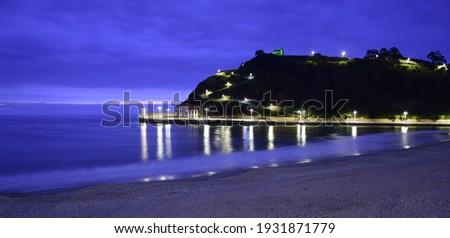 Las olas llegan a una playa de arena al anochecer, mientras al otro lado de la bahía pueden verse las farolas que iluminan el camino a una ermita sobre el acantilado Foto stock ©