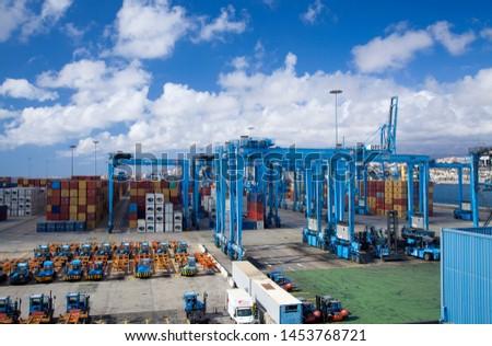 LAS PALMAS, SPAIN - July 11: Cargo containers are handled in busy cargo terminal on July 11, 2019 in Las Palmas de Gran Canaria, Spain #1453768721