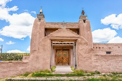 Las Trampas San Jose de Gracia church on High Road to Taos village with historic vintage adobe style building in New Mexico with door gate entrance and cross