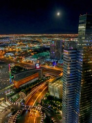 Las Vegas at night with millions of lights as shot from a 57th floor balcony shows this cityscape of colorful lights and skyscrapers under a clear sky with a full moon shining over this active city