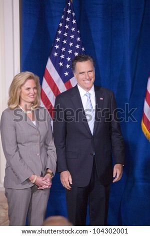 LAS VEGAS - FEB 2: Mitt Romney smiles as he stands with his wife, Ann Romney, while Donald Trump (off camera) endorses him for president at the Trump Hotel on February 2, 2012 in Las Vegas, Nevada.