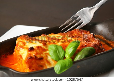 lasagna bolognese with silver fork over the wooden table
