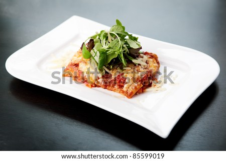 Lasagna served on a white plate with salad