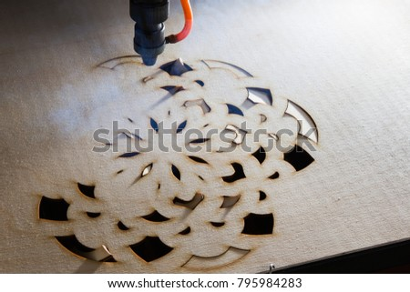 laser cuts out a tree in the form of a mandala #795984283