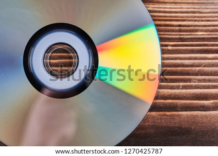 Laser discs are on a wooden table. #1270425787