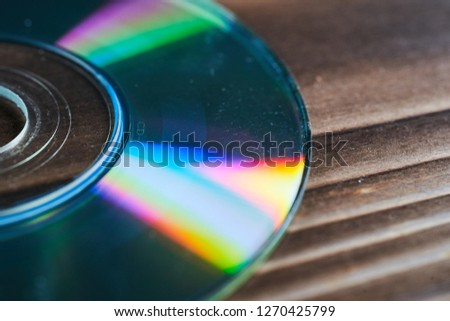 Laser discs are on a wooden table. #1270425799