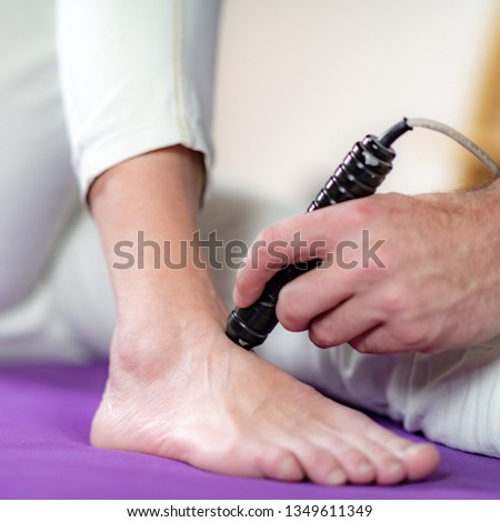 Laser Physical Therapy. Physical Therapist Treating Senior Woman's Foot in a Clinic