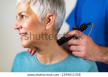 Laser Physical Therapy. Physical Therapist Treating Senior Woman's Neck in a Clinic