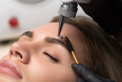 Laser removal of permanent makeup. The beautician removes the tattoo from the eyebrows.