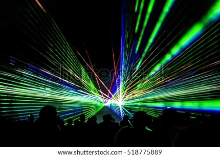 Laser show rays stream. Very colorful show with a crowd silhouette and great laser rays on great afterwork party