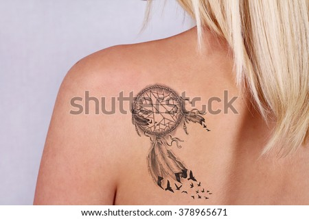 Laser tattoo removal concept. Beautiful young woman with tattoo on her back