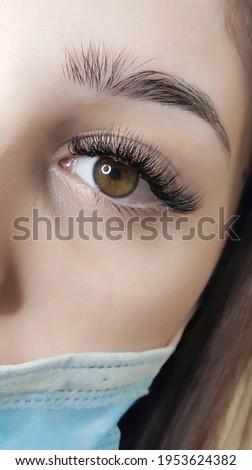 lash extensions in beauty salon, macro hazel eye in  medical mask Stock fotó ©