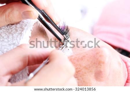 Lash making process, extreme long lashes and tweezers, woman eyelash extension