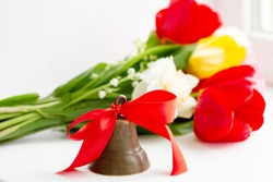 last call at school. bell with red satin ribbon, a bouquet of tulips and lilies of the valley on the table, white background