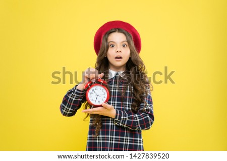 Last chance deadline. Anxious child worried about deadline on yellow background. Stressed little girl holding clock reminder of deadline. Meeting or breaking deadline.