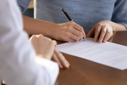 Last formality. Close up of young woman job applicant being hired on vacant place signing employment contract in presence of recruiter, female bank client putting signature under financial document