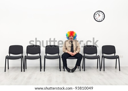 Last man standing - waiting concept with clown in business outfit