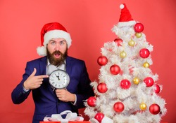 Last minute deals. Counting time till christmas. How much time left. Keep track of time. Time to celebrate. Businessman join christmas celebration. Man bearded wear suit and santa hat hold clock.