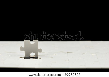 Last piece needed to complete the puzzle standing upright above the jigsaw puzzle conceptual of a solution and problem solving, low angle with a dark background with copyspace.