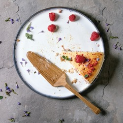 Last piece of homemade raspberry baked cheesecake on plate decorated by fresh raspberries and mint, with wooden cake server over grey textute background. Flat lay, space
