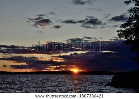 Last ray of the sun on lake Keret, Northern Karelia, Russia Stock fotó ©