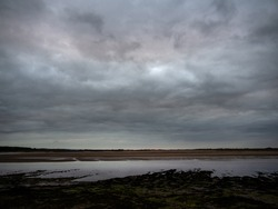 Last rays of sun and bleak landscape view from Fremington Quay over River Taw in North Devon, England, in August.