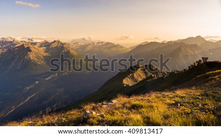 Last soft sunlight over rocky mountain peaks, ridges and valleys of the Alps at sunset. Extreme terrain landscape at high altitude in Valle d'Aosta, scenic travel destination in Italy.