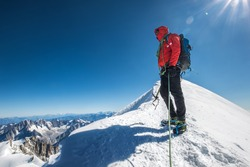 Last steps before Mont Blanc (Monte Bianco) summit 4,808 m of rope team man with climbing axe dressed mountaineering clothes, boots with crampons walking by snowy slopes with blue sky background