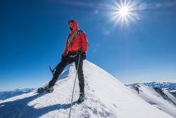 Last steps before Mont Blanc (Monte Bianco) summit 4,808m of smiling rope team man with climbing axe dressed mountaineering clothes,boots with crampons walking by snowy slopes with blue sky background