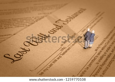 Last will and testament / legacy, inheritance or death tax concept : Miniature elder / old couple stands on a legal document form, depicts preparing to transfer properties to their heirs after death Foto stock ©