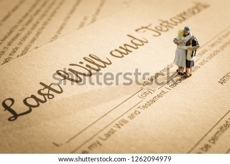 Last will and testament / legacy, inheritance or death tax concept : Miniature elder / old couple family on a legal document form, depicts preparing to transfer properties to their heirs after death Foto stock ©