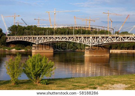 Late afternoon at Vistula river with the National Stadium under construction in the background in Warsaw, Poland. - stock photo