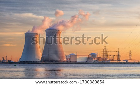 Photo of  Late afternoon scene with view on riverbank with nuclear reactor Doel, Port of Antwerp, Belgium.