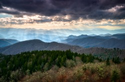 Late afternoon sunbeams shine down on the mountain peaks and ridges from a scenic overlook along the Blue Ridge Parkway in western North Carolina south of Asheville during autumn on a cold winter day.