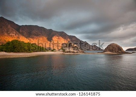 Late afternoon sunlight peaks through low clouds and into Horseshoe Bay on the southern coast of Rinca Island near Komodo National Park.  This area is known for its spectacular scuba diving.