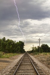 Late afternoon thunderstorms came rolling in and caught this lightning bolt striking next to the railroad track.