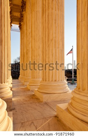 Late afternoon winter sun illuminates front of supreme court in Washington in winter with view of US flag