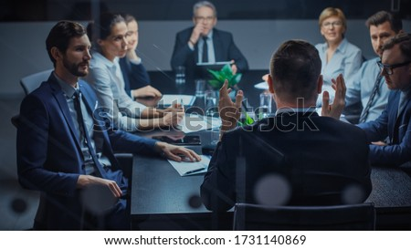 Late at Night In the Corporate Office Meeting Room: At Conference Table Executive Director Talks to a Board of Directors, Investors and Business Associates. Over the Shoulder Shot.