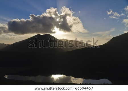 Late evening sunburst over  Llyn Cwellyn, Snowdonia, taken from the Ranger path on Snowdon, North Wales, with hills in silhouette