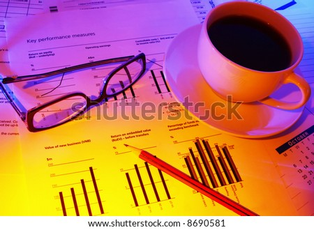 Late night checking financial performance.  Coffee for a caffeine boost, glasses and pencil on financial papers.  Warm tones.