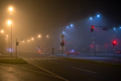 Late night in the city streets with fog, red stop lights and a red car. Reduced visibility, bad weather.
